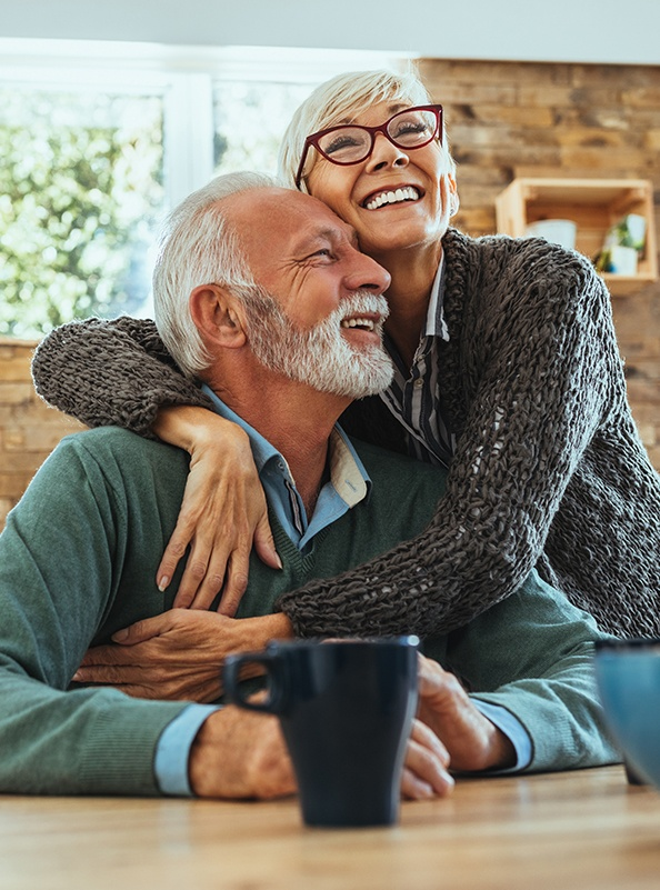 Older man and woman with dental implant supported dentures smiling