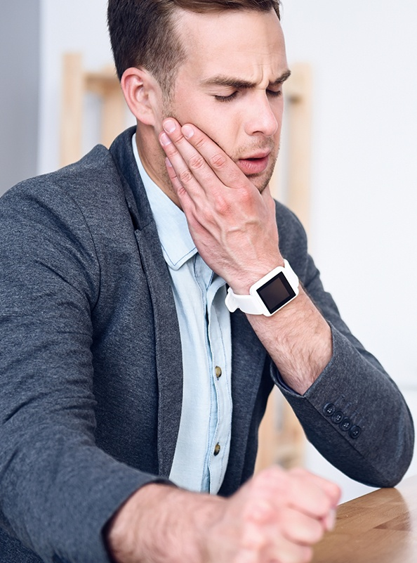 Man in need of T M J therapy holding jaw in pain