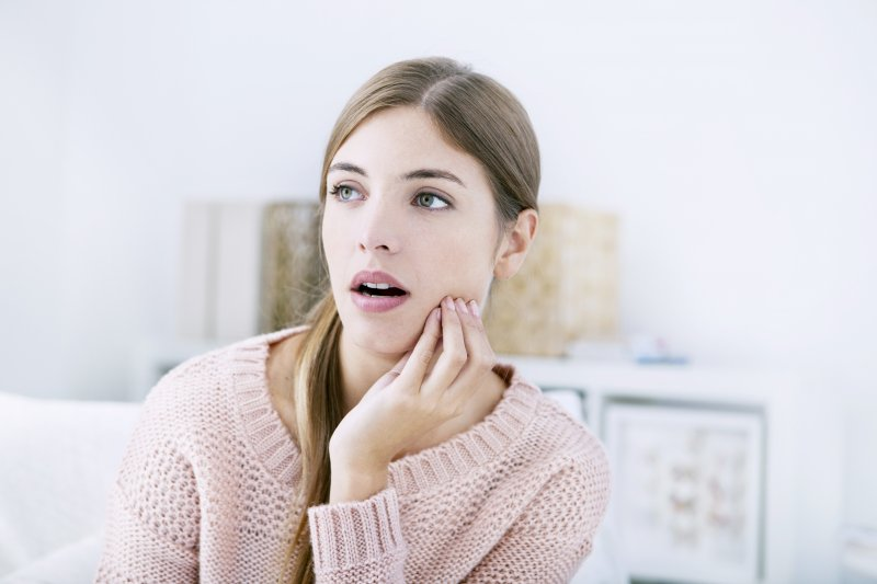 Woman in sweater with jaw pain due to TMD